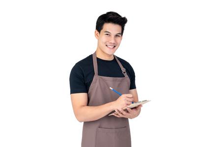 Foto de Young handsome smiling Asian man barista taking order with service mind, studio shot isolated on white background - Imagen libre de derechos