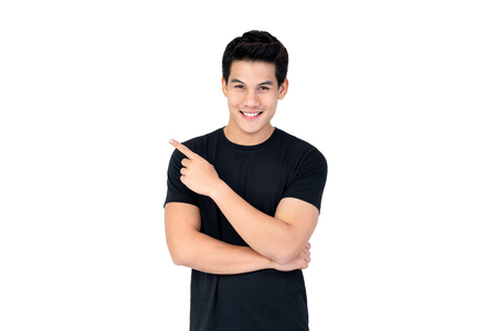 Foto per Isolated portrait of  happy smiling Asian man wearing casual black t-shirt pointing hand to empty space aside studio shot white background - Immagine Royalty Free