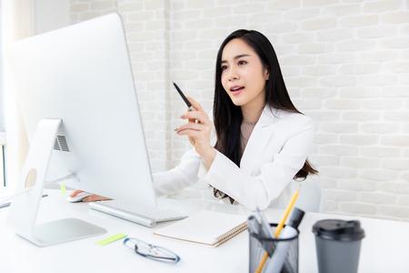Foto de Smart beautiful Asian businesswoman working on computer searching for information online in the office - Imagen libre de derechos