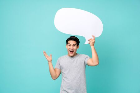 Foto de Excited young Asian man holding speech bubble with empty space for text studio shot isolated on light blue background - Imagen libre de derechos