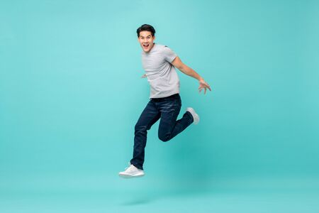 Photo pour Energetic happy young Asian man in casual clothes jumping, studio shot isolated in light blue background - image libre de droit