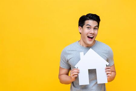 Photo pour Portrait of young happy excited Asian man holding paper home for real estate concept - image libre de droit