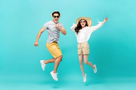 Photo pour Playful energetic Asian couple in summer beach casual clothes jumping isolated on light blue background studio shot - image libre de droit