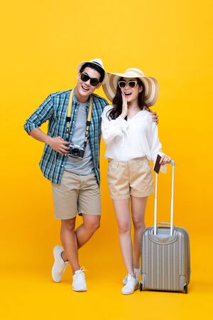 Foto per Happy excited young Asian couple tourists in colorful yellow background - Immagine Royalty Free