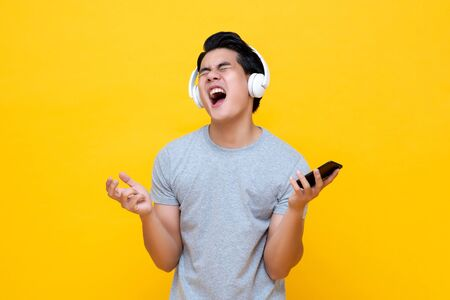 Photo pour Young Asian man wearing headphones singing and screaming while listening to rock music from smartphone - image libre de droit