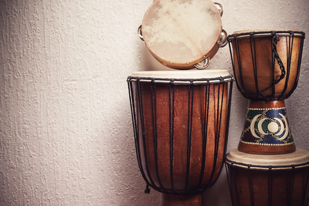 Photo for Various djembes and tambourine in front of a rustic wall. - Royalty Free Image