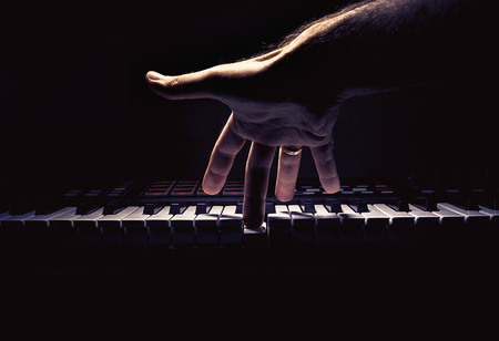 Photo pour Playing a keyboard, one male hand playing, accentuated contrasts. - image libre de droit