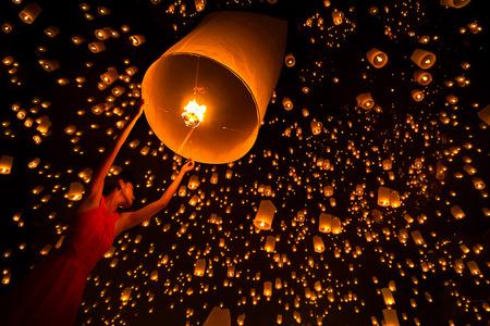 Foto de Young woman release sky lanterns to worship buddha's relics in yi peng festival, Chiangmai thailand - Imagen libre de derechos