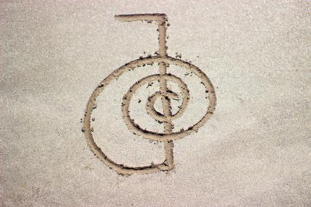 Foto de Reiki healing symbol cho ku rei on sand. Alternative medicine concept. - Imagen libre de derechos