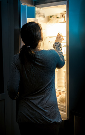 Portrait of hungry woman looking in fridge at late night