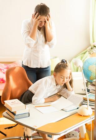 Foto de Frustrated young mother looking daughter sleeping while doing homework - Imagen libre de derechos