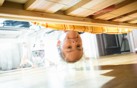 Photo pour Portrait of brunette smiling girl looking under bed at morning - image libre de droit