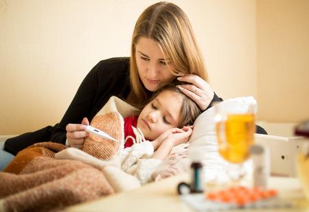 Foto de Young mother checking temperature of sick daughter lying in bed - Imagen libre de derechos