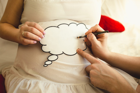 Photo for Closeup of photo of man writing on paper sign on wife's pregnant abdomen - Royalty Free Image