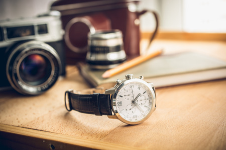 Photo pour Closeup toned shot of male watches lying on table against photography retro set - image libre de droit