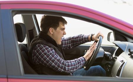 Foto de Closeup portrait of aggressive male driver honking in traffic jam - Imagen libre de derechos