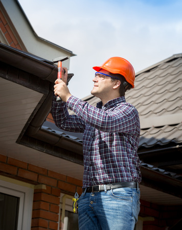 Photo pour Portrait of young handyman repairing house roof with nails and hammer - image libre de droit