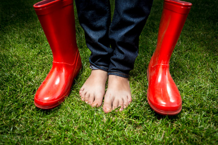 Closeup photo of female feet standing on green grass next to red rain boots