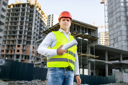 Foto de Portrait of architect in red hardhat posing on building site - Imagen libre de derechos