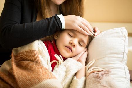 Foto de Closeup photo of caring mother holding head on sick daughter forehead - Imagen libre de derechos