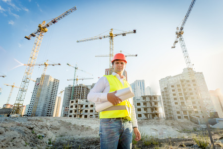Foto de Portrait of construction inspector posing with blueprints on building site - Imagen libre de derechos