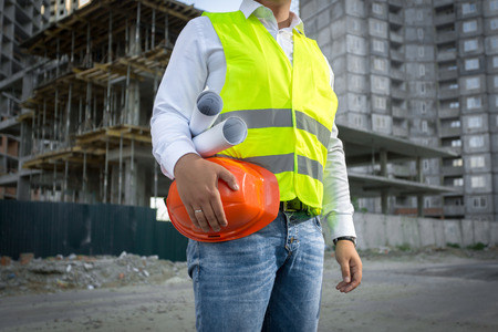 Foto de Architect in yellow safety jacket posing with red helmet at construction site - Imagen libre de derechos