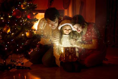 Photo pour Happy family looking inside of magic Christmas gift box - image libre de droit