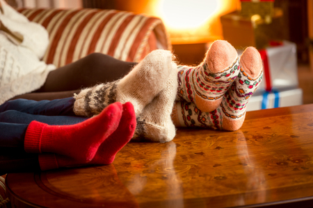 Foto de Closeup conceptual photo of family warming feet at fireplace - Imagen libre de derechos