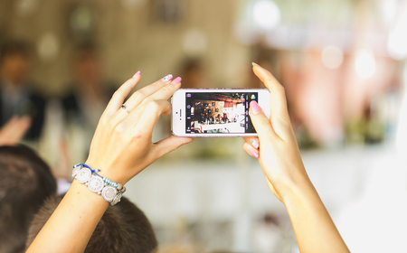 Photo for Closeup photo of woman making photo on mobile phone at wedding ceremony - Royalty Free Image