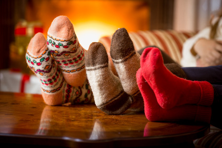 Foto de Closeup photo of family feet in wool socks at fireplace - Imagen libre de derechos