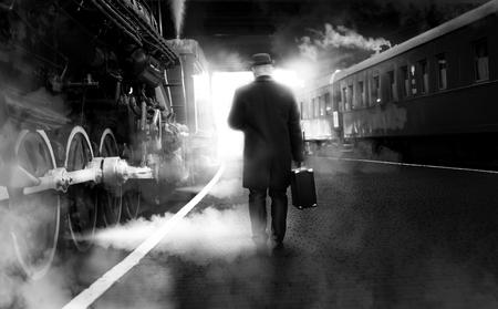 Foto de Black and white photo of man in vintage clothes walking on old railway station - Imagen libre de derechos