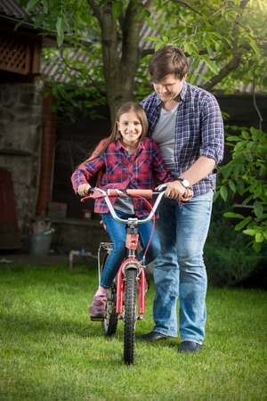 Happy smiling girl learning how to ride a bicycle with her father at park