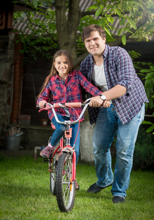 Happy young man and girl riding a bicycle relaxing at park