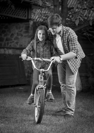 Monochrome image of happy father teaching his daughter how to ride a bicycle