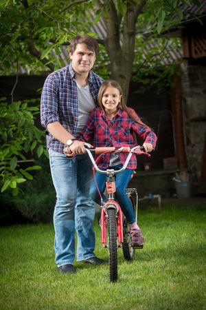 Young man and girl riding a bicycle relaxing at park