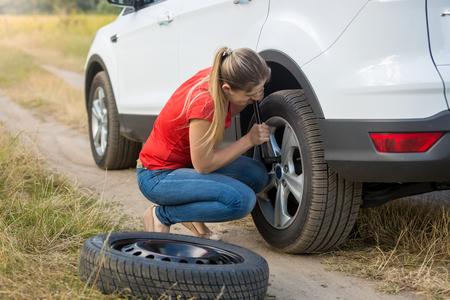 Photo pour Young woman changing flat tire in field - image libre de droit