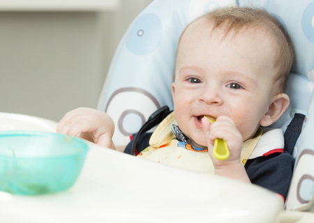 Photo for Adorable 9 months old boy eating in highchair at kitchen - Royalty Free Image