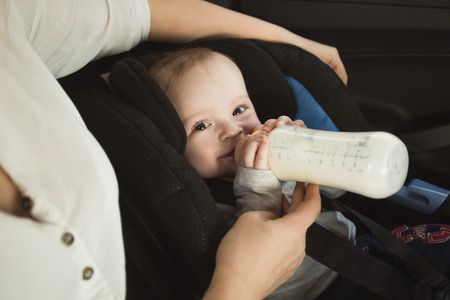 Photo pour Portrait of baby boy drinking milk from bottle on car back seat - image libre de droit