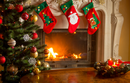 Foto de Empty wooden table in front of decorated fireplace and Christmas tree. Place for text. - Imagen libre de derechos