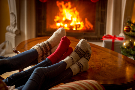 Photo pour Male and female feet in woolen socks warming at burning fireplace - image libre de droit