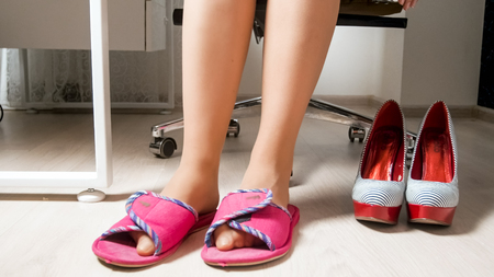 Photo pour Young woman in office wearing comfortable slippers instead of high heels shoes - image libre de droit