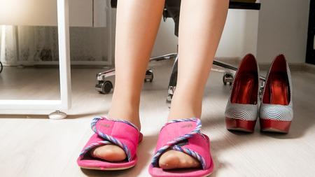 Photo pour Closeup photo of young woman in slippers under office desk - image libre de droit