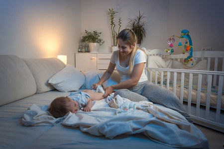 Photo pour Beautiful young mother changing diapers to her baby boy at night - image libre de droit