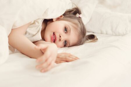 Foto de Little cheerful girl 4 years old smiles and lies on bed on under white blanket, lifestyle - Imagen libre de derechos