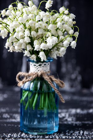 Photo pour Lily of the valley on a dark wooden background. Lily of the valley bouquet. Space for text. - image libre de droit