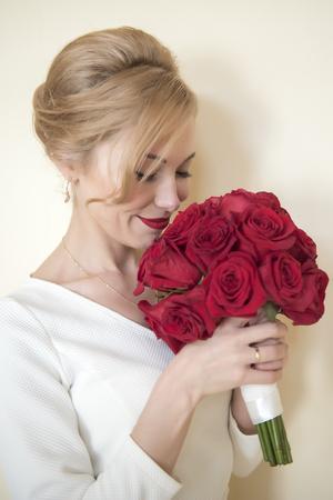 Foto de Young beautiful bride with the bouquet of red roses - Imagen libre de derechos