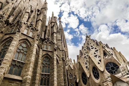 Foto de View from low angle on side of Sagrada Familia with blue sky and white clouds - Imagen libre de derechos