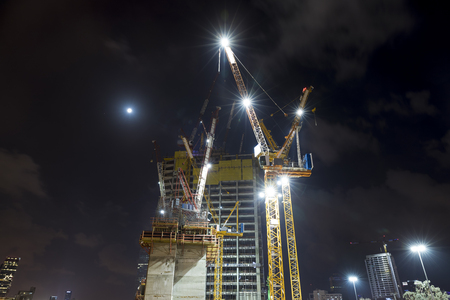 Photo pour Construction building site with tower cranes building under construction lighted with projectors at night from low angle - image libre de droit