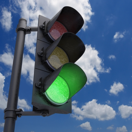 Traffic Light in a blue sky with only the green light on.