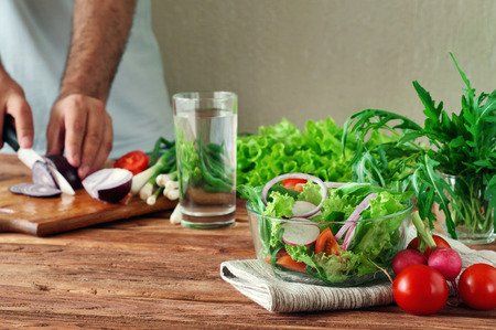 Photo pour Fresh salad of summer vegetables in a deep bowl of glass. Arugula, lettuce, radishes, onions, cherry tomatoes. In the background male hand sliced onions on cutting board. - image libre de droit
